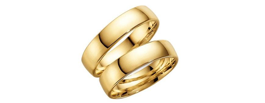 Släta guldringar som förlovningsringar och vigselringar